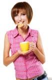 сдерживая чай кренделя девушки чашки милый Стоковая Фотография