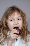 сдерживая шоколад - покрынная девушка печенья немногая Стоковые Фотографии RF