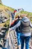 СЕВЕРНАЯ ИРЛАНДИЯ, ВЕЛИКОБРИТАНИЯ - 8-ОЕ АПРЕЛЯ 2019: Вспугнутые туристы пересекают опасный но красивый мост веревочки Carrick-a- стоковые фотографии rf