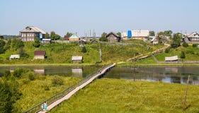северное русское село Летний день, река, старые коттеджи на побережье Стоковое Изображение