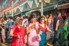 СЕВИЛЬЯ, ИСПАНИЯ - 25-ое апреля: Женщины в платье стиля фламенко на Стоковая Фотография RF