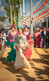 СЕВИЛЬЯ, ИСПАНИЯ - 25-ое апреля: Женщины в платье стиля фламенко на Стоковые Изображения