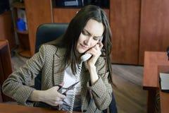 Секретарша девушки говоря на телефоне в офисе хочет пару ножниц отрезать провод телефона трудная работа Стоковое Изображение RF