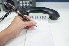 Секретарша принимает примечание с предпосылкой телефона IP стоковая фотография