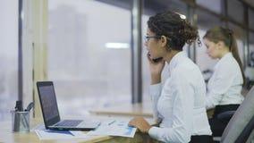 Секретарша смешанной гонки работая на проекте и говоря на телефоне в офисе сток-видео