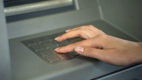 Секретный номер женщины входя в для того чтобы проверить счет в банк и разделить деньги от ATM стоковое фото