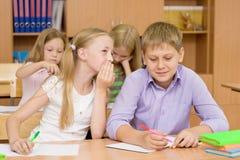 Секреты девушки шепча мальчика в классе Стоковое Фото