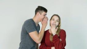 Секрет милой девушки шепча в ухе ее смеясь над друга на белой предпосылке - концепции приятельства Стоковые Фотографии RF