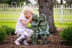Секрет милой маленькой девочки шепча к маленьким друзьям статуи сада стоковая фотография