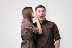 Секрет молодой женщины шепча к ее парню стоковое изображение rf