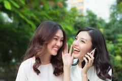 Секрет молодой азиатской женщины шепча в ухо друзей пока она Стоковые Фото