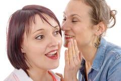 Секрет привлекательной молодой женщины шепча в ухе друга Стоковое Изображение