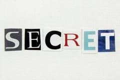 Секрет слова отрезанный от газеты на белой бумаге Стоковое Изображение