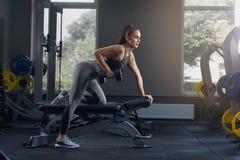 Сексуальная атлетическая женщина нагнетая вверх muscles с гантелями на спортзале стоковое изображение rf