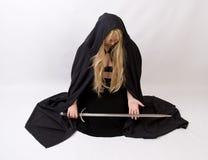 Сексуальная белокурая женщина в черном плаще стоковые изображения rf