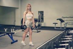Сексуальная горячая белокурая девушка бикини фитнеса с совершенным телом формы и батт представляя и ослабляя в спортзале спортсме Стоковые Фото