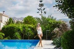 Сексуальная, горячая и модная белокурая модельная девушка в белых стильных купальнике и солнечных очках наслаждается солнцем и пр Стоковые Фото