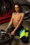 Сексуальная девушка в гараже с автошинами велосипеда Стоковая Фотография RF