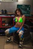 Сексуальная девушка в гараже с автошинами велосипеда Стоковые Фото