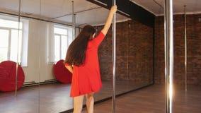 Сексуальная девушка в красном танце поляка платья Закручивать вокруг поляка видеоматериал