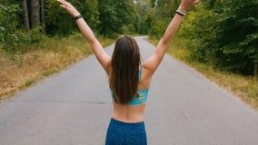 Сексуальная девушка идя на дорогу в фитнесе outdoors леса съемка с steadicam акции видеоматериалы