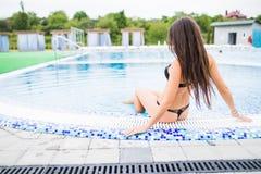 Сексуальная девушка принимает sunbath в бассейне Призвание лета стоковое изображение