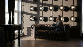Сексуальная девушка сидит на софе видеоматериал