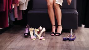 Сексуальная, длинн-шагающая женщина пробуя на черноте высоко-накренила сандалии в стильном магазине, бутике движение медленное Ко сток-видео