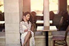 сексуальная женщина Женщина в белом платье внешнем Сексуальная женщина сидит самостоятельно в кафе улицы Фотомодель с взглядом оч Стоковая Фотография RF