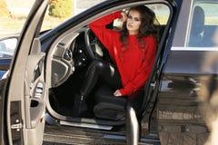 Сексуальная женщина в элегантных одеждах представляя в роскошном автомобиле Стоковое фото RF
