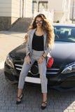 Сексуальная женщина в элегантных одеждах представляя в роскошном автомобиле Стоковые Фотографии RF