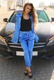 Сексуальная женщина в элегантных одеждах представляя в роскошном автомобиле Стоковые Изображения