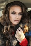 Сексуальная женщина в элегантных одеждах представляя в роскошном автомобиле Стоковое Изображение