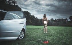 Сексуальная женщина двигая далеко от автомобиля и цветков Стоковое фото RF