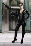 Сексуальная женщина держа пушку нося черное кожаное платье стоковые изображения rf