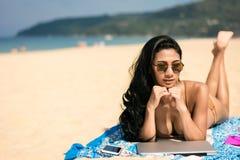 Сексуальная женщина загорая на пляже с мобильным телефоном компьтер-книжки пока ослабляющ по выходным стоковые изображения