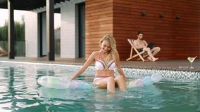 Сексуальная женщина имея потеху в бассейне Усмехаясь модель ослабляя в бассейне акции видеоматериалы
