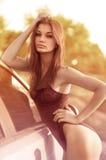 Сексуальная женщина и автомобиль на зеленом поле Стоковые Фотографии RF