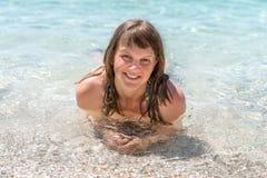 Сексуальная женщина лежит на пляже около Адриатического моря в Хорватии стоковая фотография