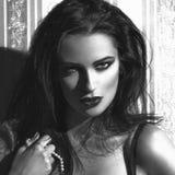 Сексуальная женщина на винтажной стене с портретом жемчугов черно-белым стоковая фотография rf