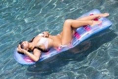 Сексуальная женщина на цветастом поплавке бассеина стоковая фотография