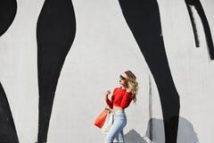 Сексуальная и красивая белокурая модельная девушка с совершенным телом и в солнечных очках, в стильной красной фуфайке и в модном стоковая фотография rf