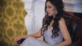 Сексуальная и привлекательная модель в сером классическом платье представляя для фотографа сидя в стуле видеоматериал
