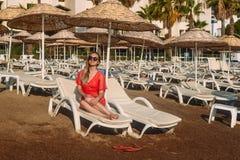 Сексуальная кавказская женщина в красной прозрачной тунике пляжа лежа на белом lounger на пляже стоковые изображения