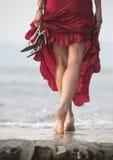 Сексуальная красная одетьнная женщина гуляет на влажный камень рядом с Стоковое фото RF