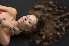 Сексуальная лежа девушка с длинними курчавыми волосами и рукой на шеи Стоковое Изображение