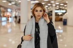 Сексуальная милая стильная молодая белокурая женщина с серыми глазами в роскошном сером пальто с винтажным шарфом с модной сумкой стоковая фотография