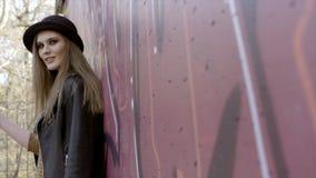 Сексуальная модельная женщина в черной нося шляпе, стоящ и представляющ около стены E Стильная молодая женщина в положении шляпы стоковые фотографии rf