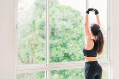 Сексуальная молодая азиатская тренировка руки простирания девушки на спортивном клубе фитнеса или домашнем спортзале Класс йоги а Стоковая Фотография RF