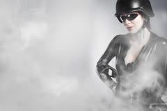 Сексуальная молодая держа пушка с дымом стоковые изображения